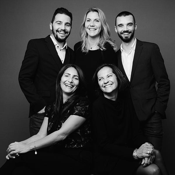 Photo d'équipe en noir et blanc prise en studio de cinq personnes joyeuses