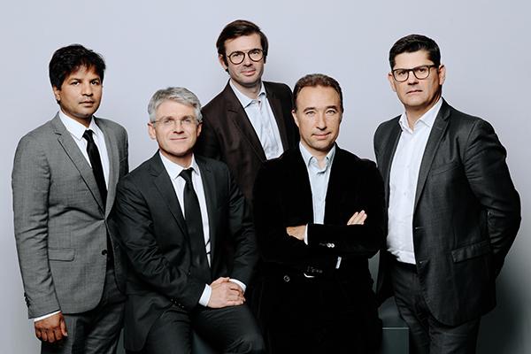 Photo de groupe en studio de cinq hommes en costumes cravates sur fond blanc