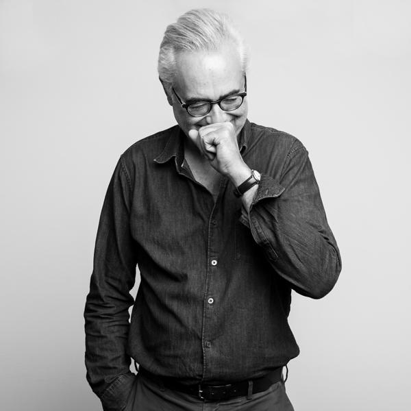 un homme qui porte des lunettes et qui a un fou rire sur un fond blanc