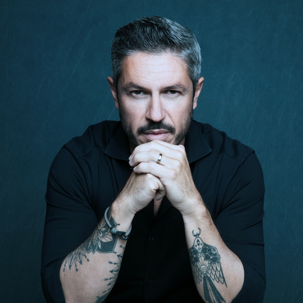 un homme assis les mains au visages avec des tatouages sur les bras sur un fond bleu