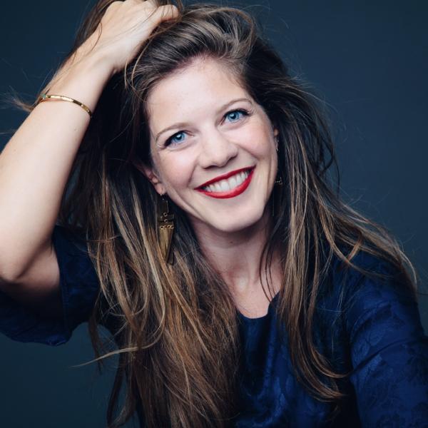 gros plan d'un visage de femme très souriante avec la main dans ses cheveux longs