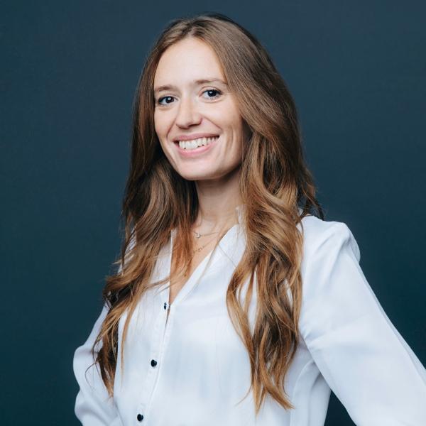 jeune femme rousse souriante avec une chemise blanche sur fond bleu