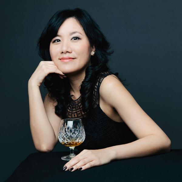 buste d'une femme brune élégante assise à une table avec un verre de whisky sur fond sombre